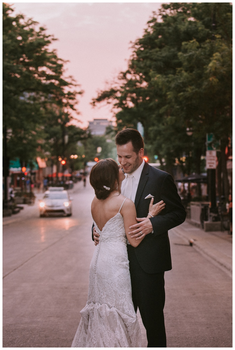 wedding couple dances in downtown madison state street at sunset on their wedding day