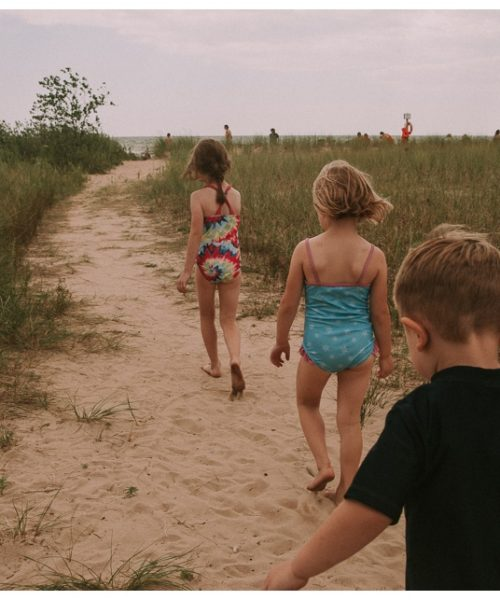 Three kids walk along the beach.